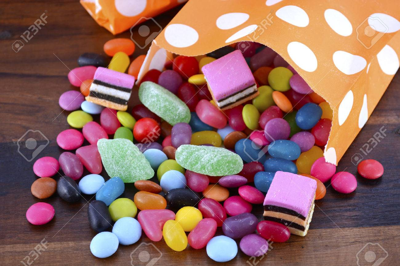 Halloween Party Trick of Treat Candy with candy flowing from orange polka dot party favor bag on dark wood background. - 46091687