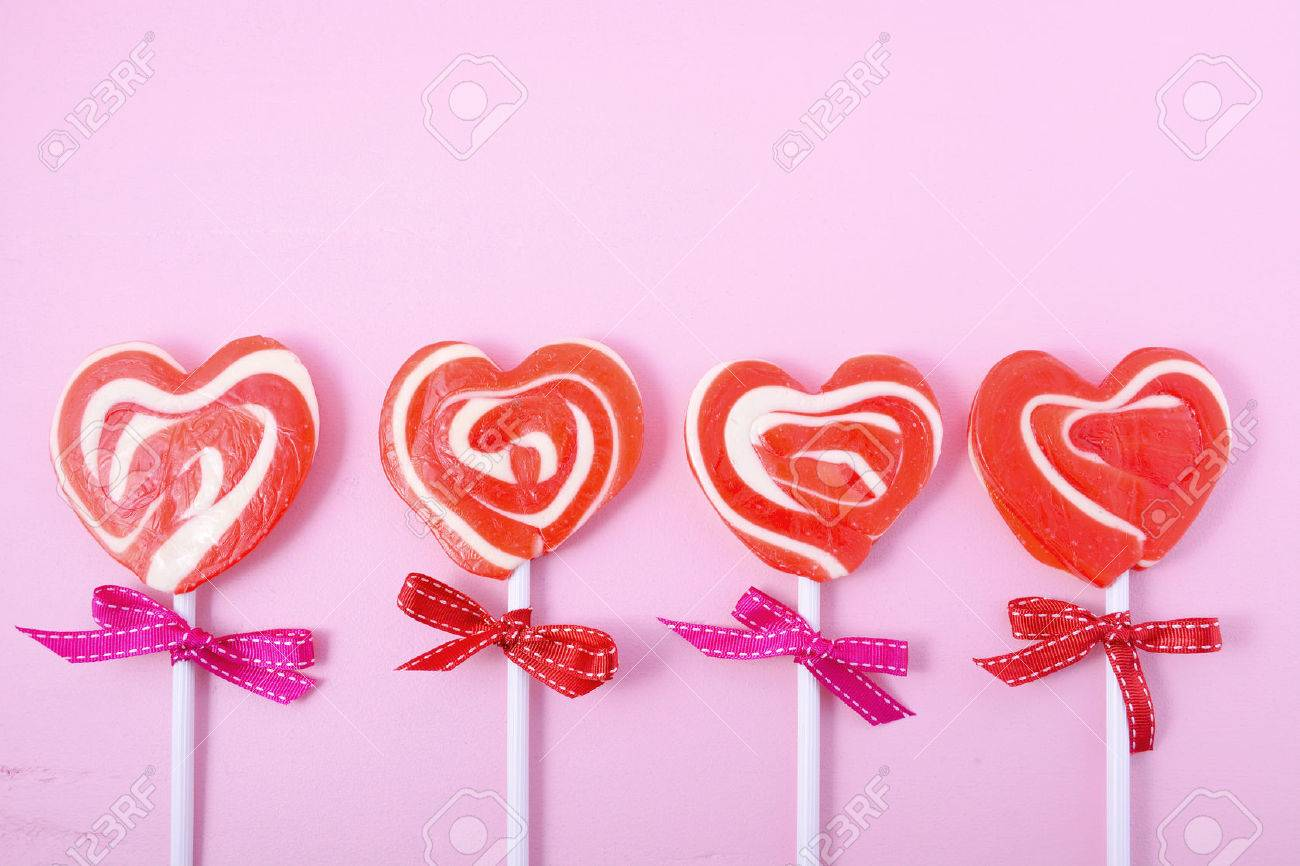Happy Valentines Day Candy With Red Heart Shape Lollipops On Pink Wood  Background. Stock Photo