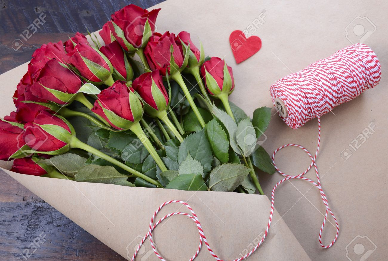 Wrapping Valentine Red Roses In Brown Paper On Dark Wood Background