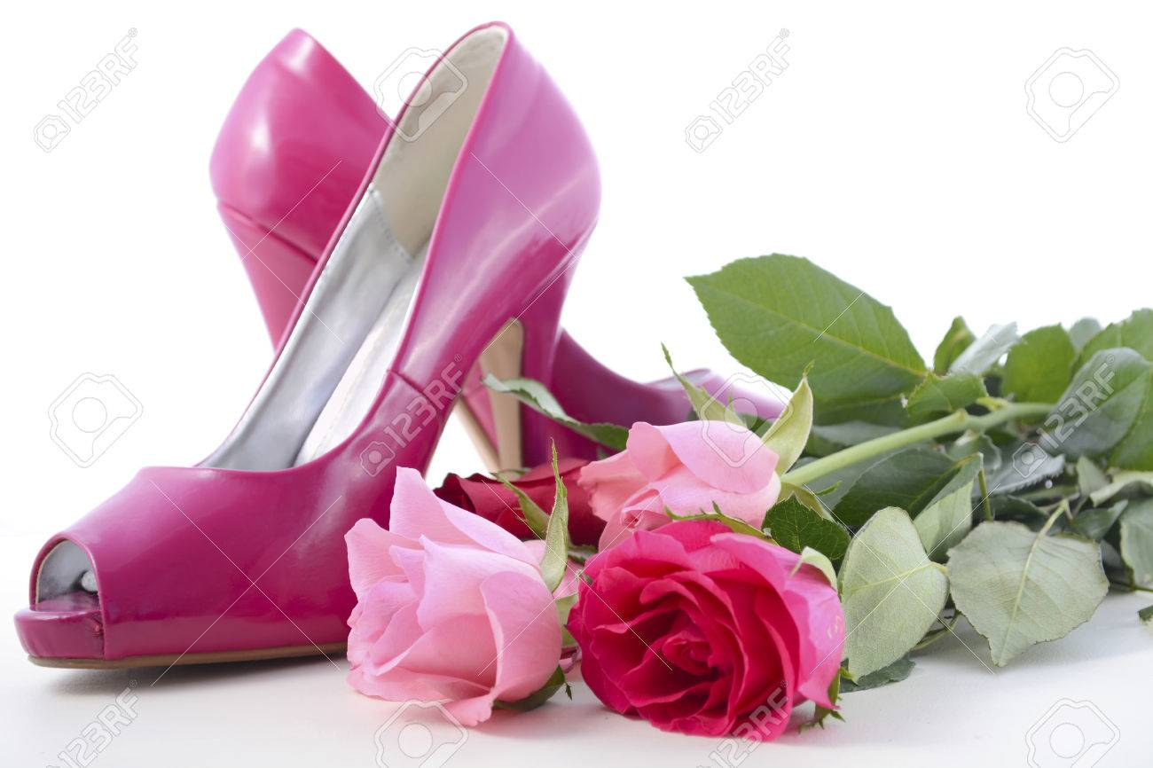 d8eb1538443 Feminine pink high heel shoes with roses on white wood table..