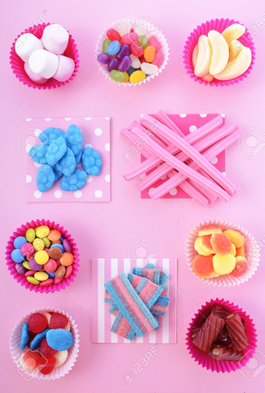 fondo brillante caramelos de colores en la mesa de madera de color rosa para el truco