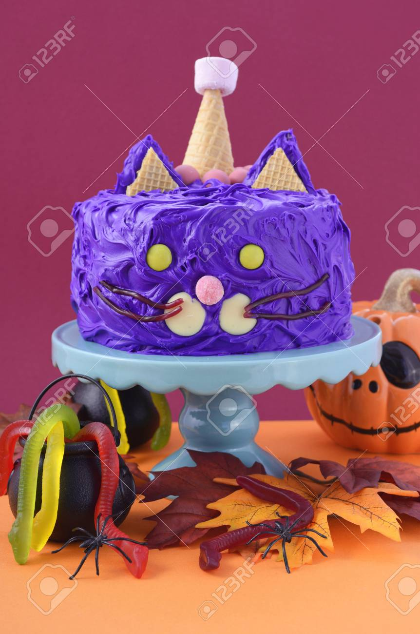 Happy Halloween Cat Cake Party Food With Purple Frosting And Candy Decorations On Colorful Table