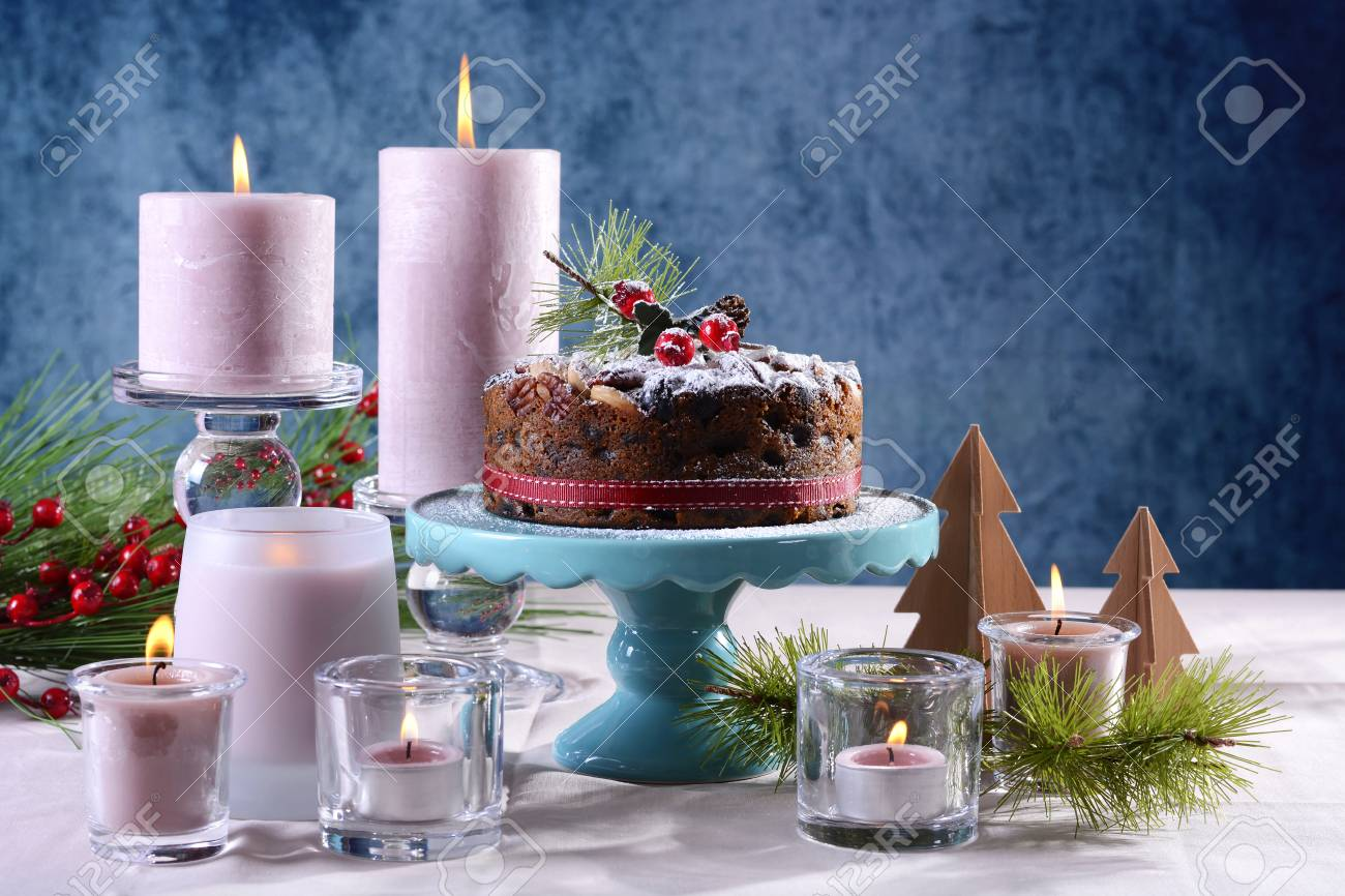 Festive holiday table with English style Christmas fruit cake with glamorous table setting with pink candles & Festive Holiday Table With English Style Christmas Fruit Cake ...
