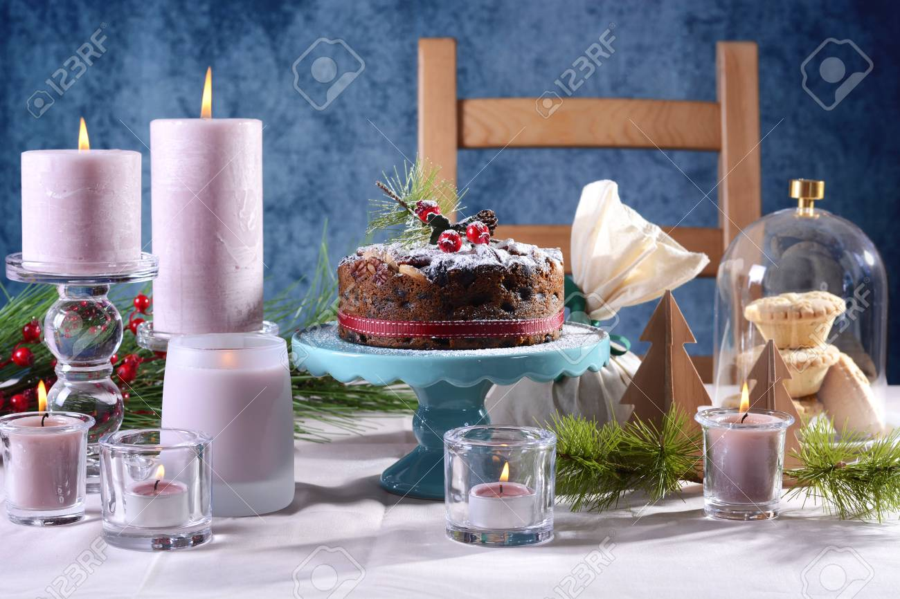 Festive holiday table with English style Christmas fruit cake with glamorous table setting with pink candles & Festive Holiday Table With English Style Christmas Fruit Cake ...