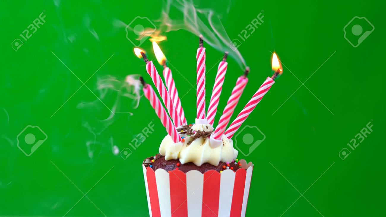 Happy Birthday Cupcake With Colorful Candles Against A Green Background Blowing Out Stock Photo