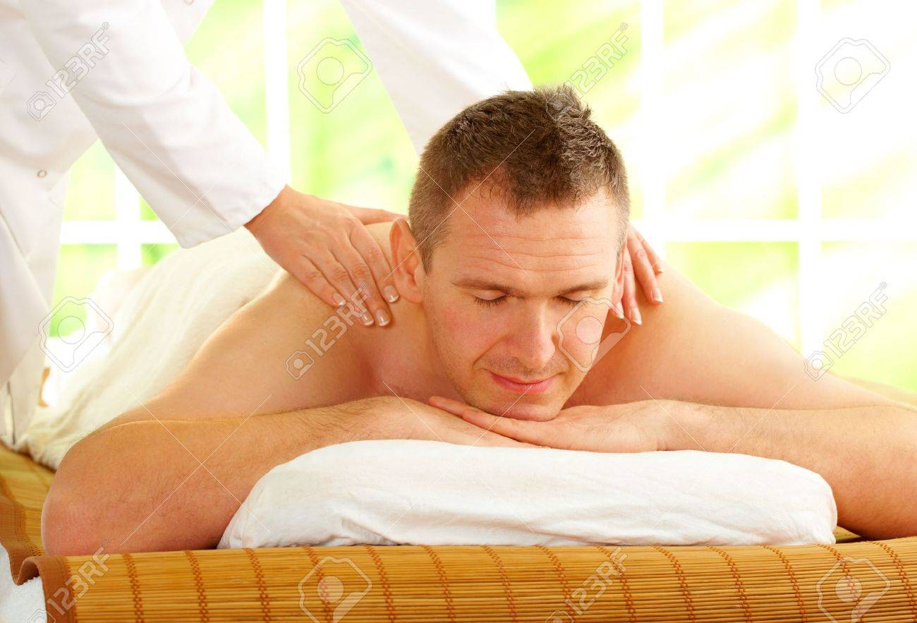Male enjoying massage treatment with female hands on his shoulder and back, Stock Photo - 6482383