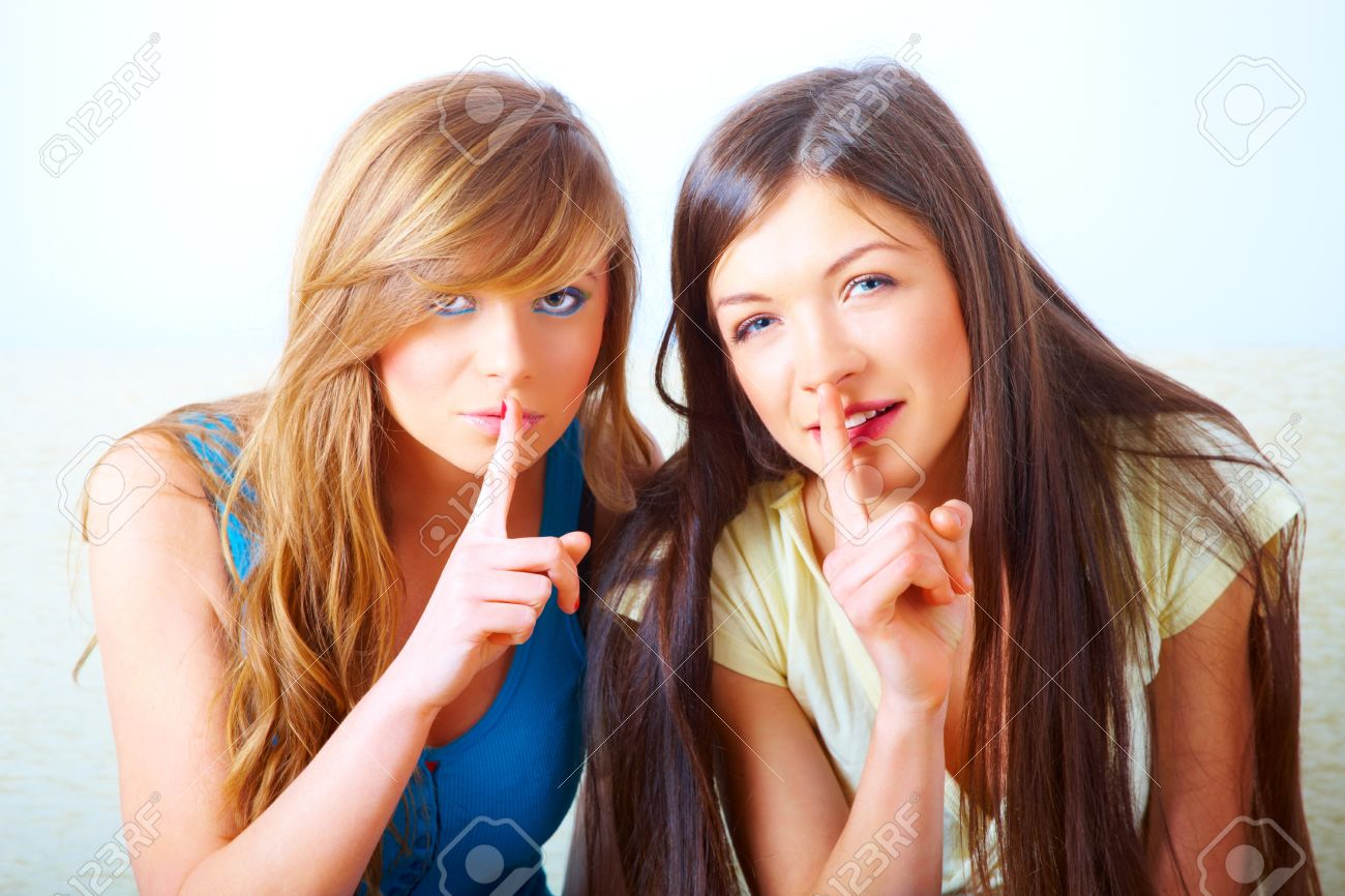 Two beautiful young girls gesturing for quiet with fingers over mouth shushing. Conceptual image illustrating secret or mystery Stock Photo - 8887486