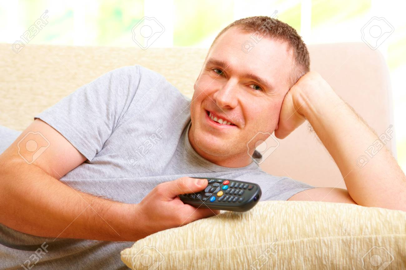 Relaxed handsome man smiling lying on sofa with remote control handheld, watching television in home Stock Photo - 8887281