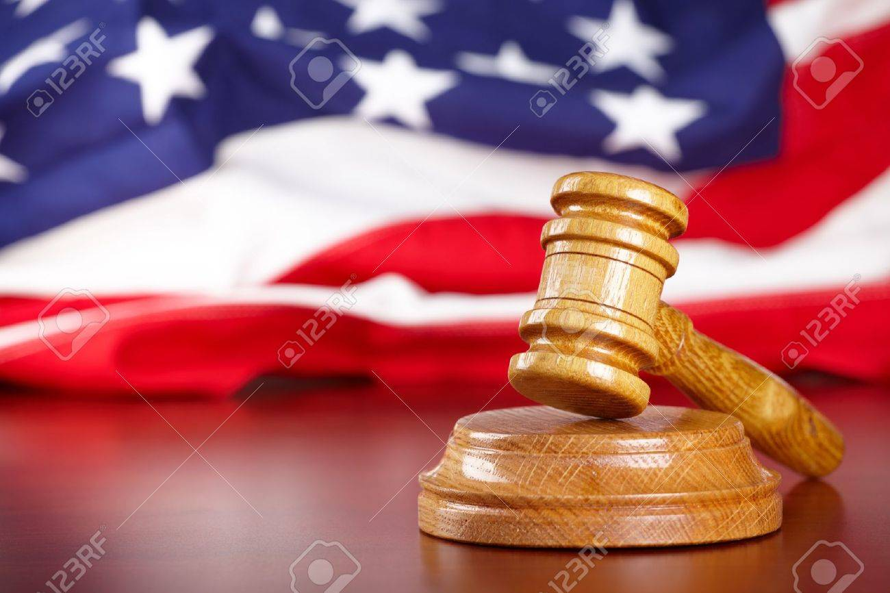 Judges wooden gavel with USA flag in the background Stock Photo - 8887440