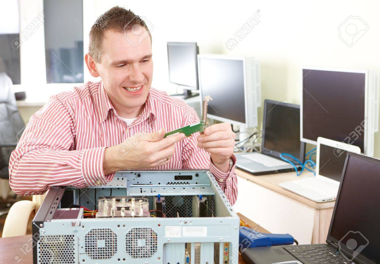 Repairman working with computer with a part in hands. Monitors and other laptops in the background waiting for service. Stock Photo - 8987869