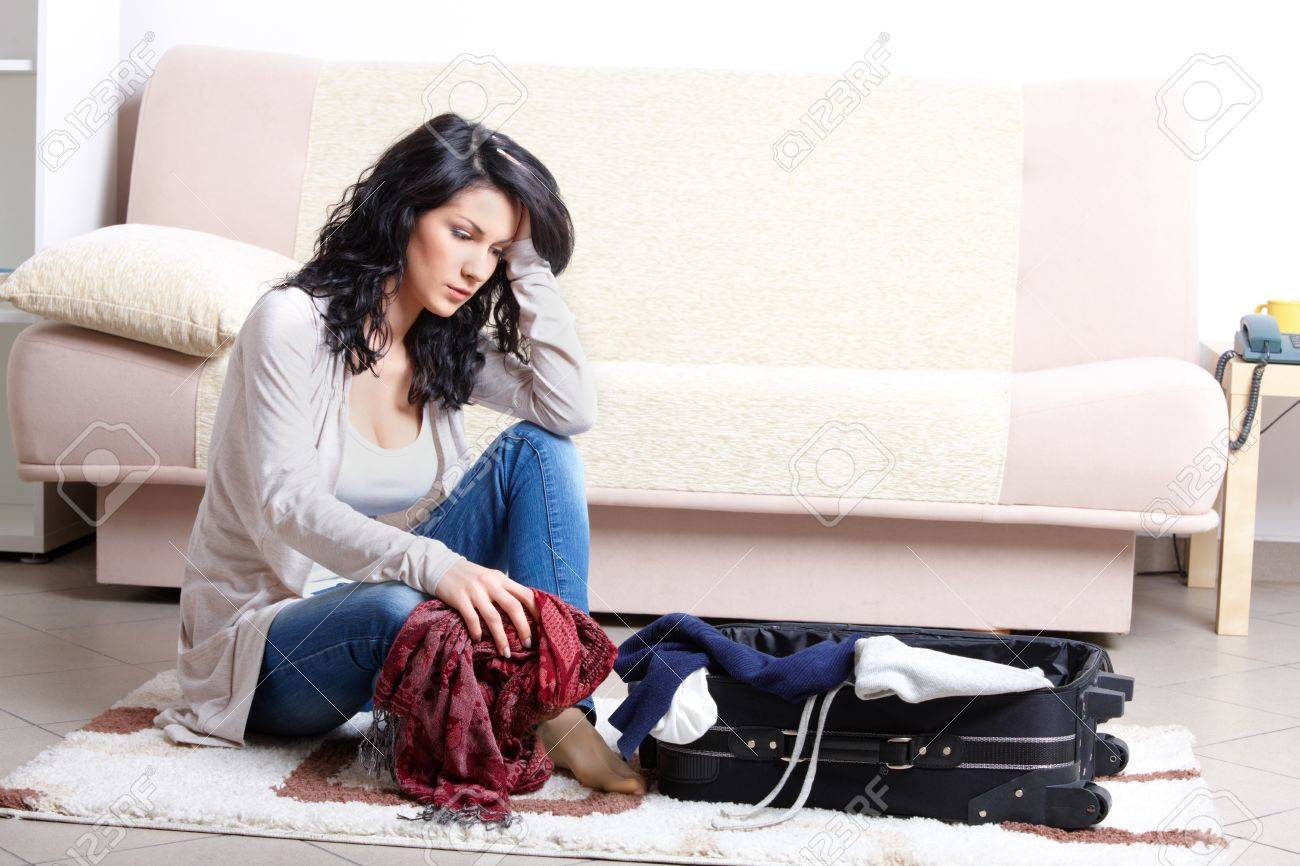 Young girl preparing her luggage before travel. She is in doubt of what to pack Stock Photo - 9502660