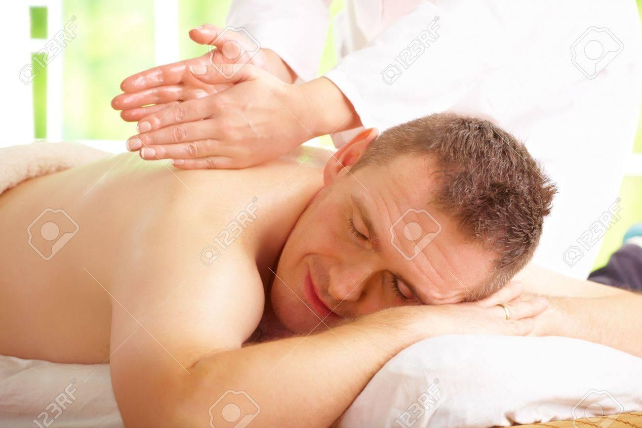 Man enjoying massage treatment with female hands on his back Stock Photo - 9770237