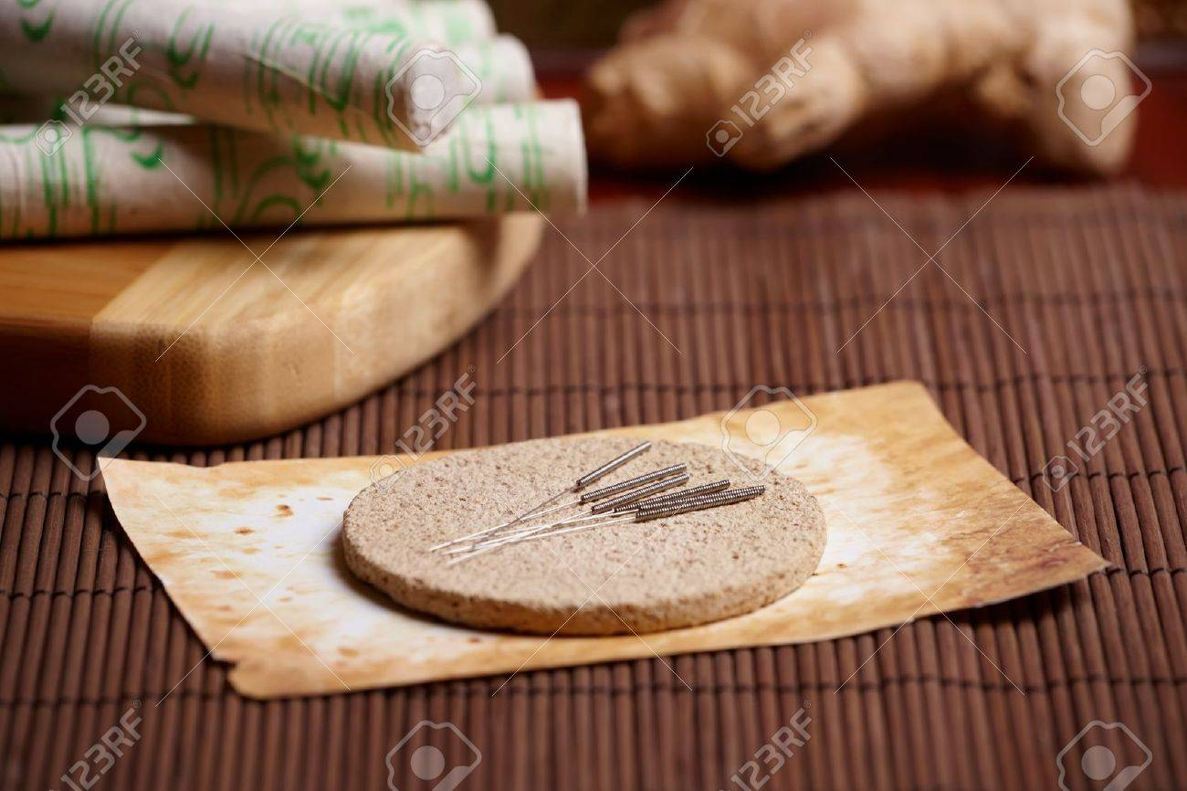 Acupuncture needles laying on the stone mat, moxa sticks on wooden desk and fresh ginger in the background. TCM Traditional Chinese Medicine concept photo Stock Photo - 11844431