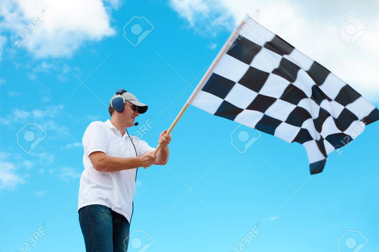 Man with headset holding and waving a checkered flag on a raceway Stock Photo - 12250559