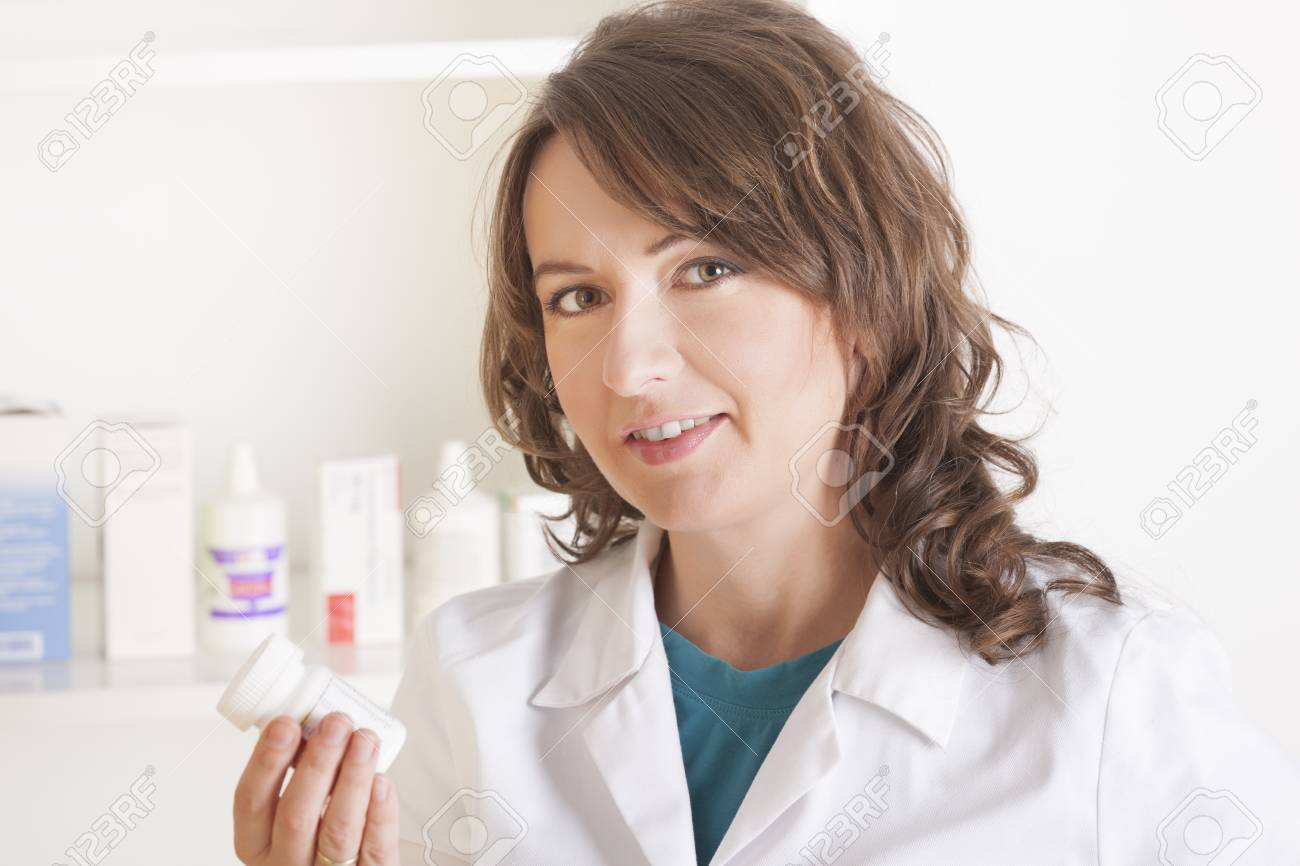A cheerful young woman pharmacist with a bottle of drugs standing in pharmacy drugstore Stock Photo - 16661256