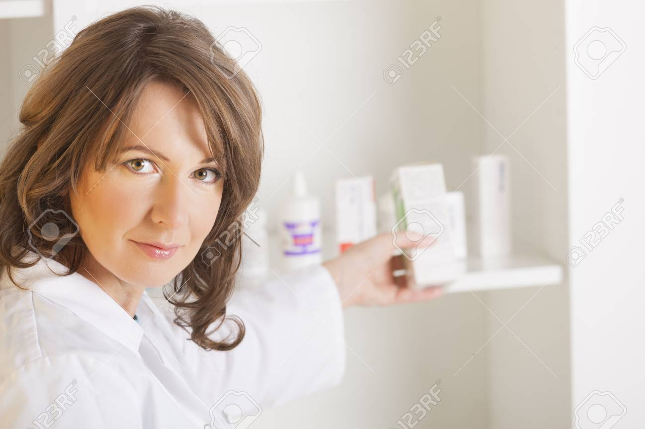 A cheerful young woman pharmacist with a bottle of drugs standing in pharmacy drugstore Stock Photo - 16732401