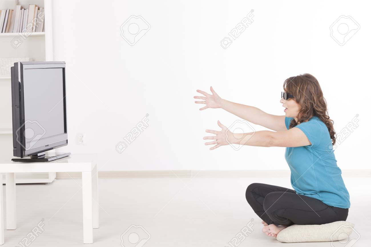 Beautiful young woman watching 3D TV in 3d glasses and trying to catch sometching Stock Photo - 17082666