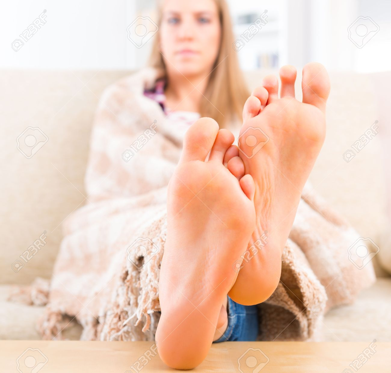 young feet Young woman covered with blanket sitting on the sofa at home Focus on feet  Stock Photo