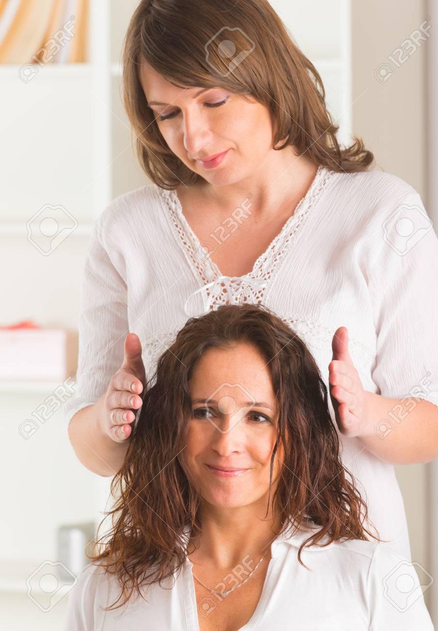 Professional Reiki healer doing reiki treatment to young woman Stock Photo - 27115247