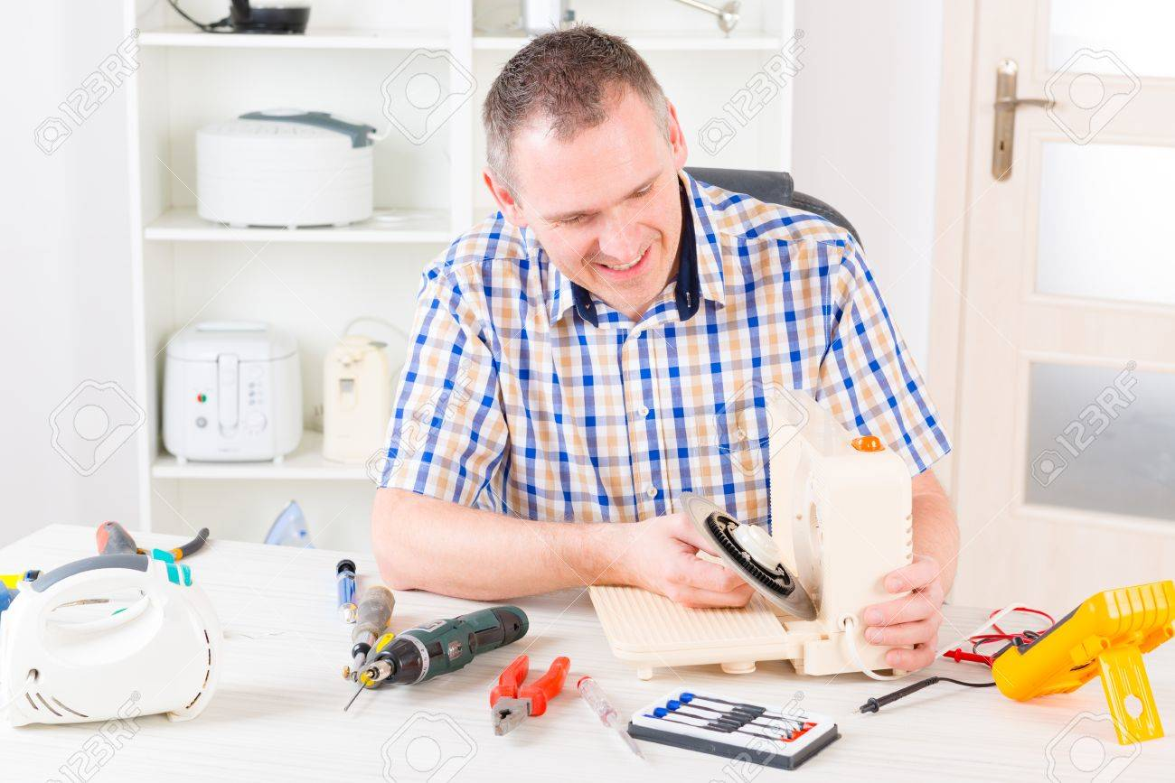 Home Appliance Service Man Repairing A Slicing Machine At Home Appliance Service Workshop