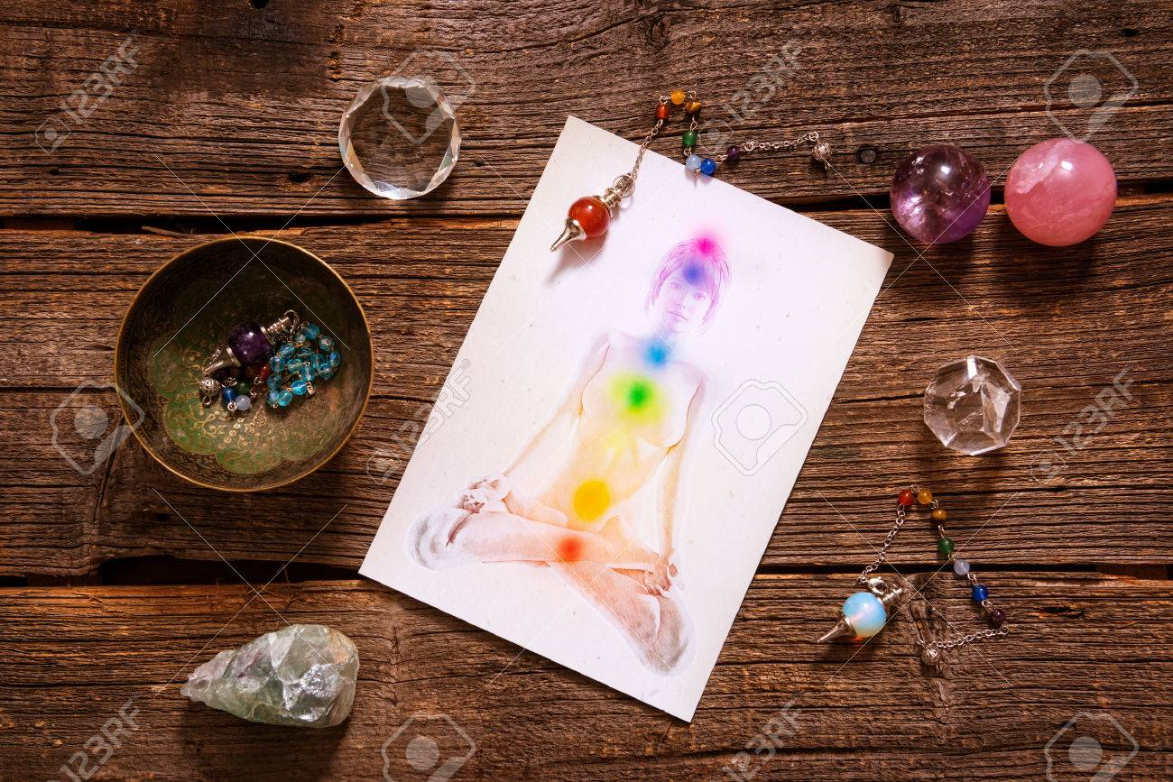 Chakras illustrated over human body with natural crystals and pendulum - 52304301