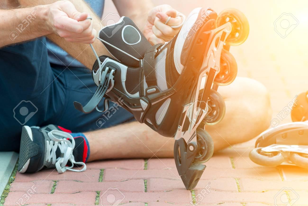 Man preparing for roller blading, putting on rollerblades. - 62052273