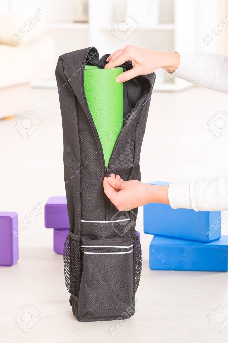 Putting a yoga mat inside a special yoga bag Stock Photo - 70258889 bd6fa0736be2b