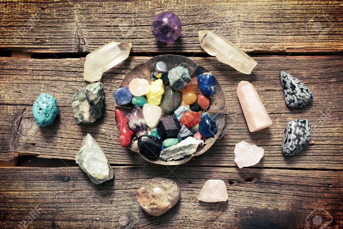 Multiple semi precious gemstones on wooden boardfluorite, quartz, obsidian, rose quartz and many other - 73498605