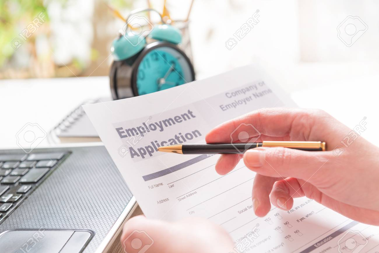 Blank Employment Application Form In Hands On A Desk Stock Photo ...
