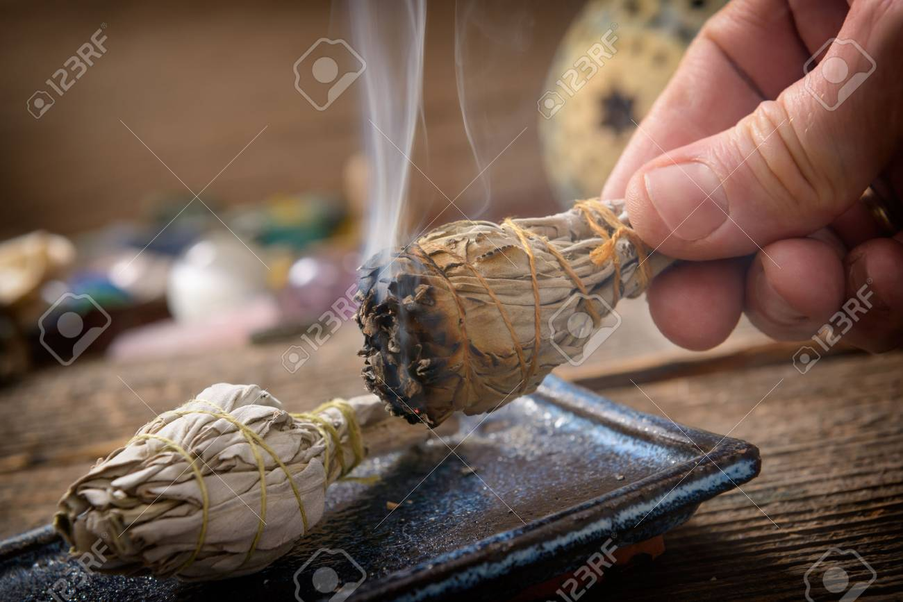 Man's hand with burning natural white sage incense - 74353630