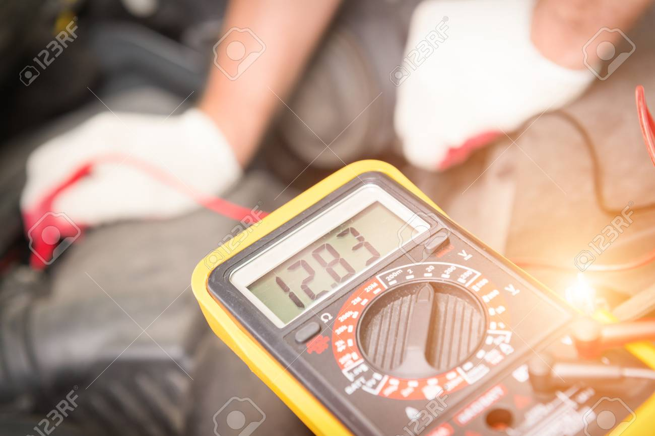 Car mechanic uses a multimeter to check car battery voltage - 82272829