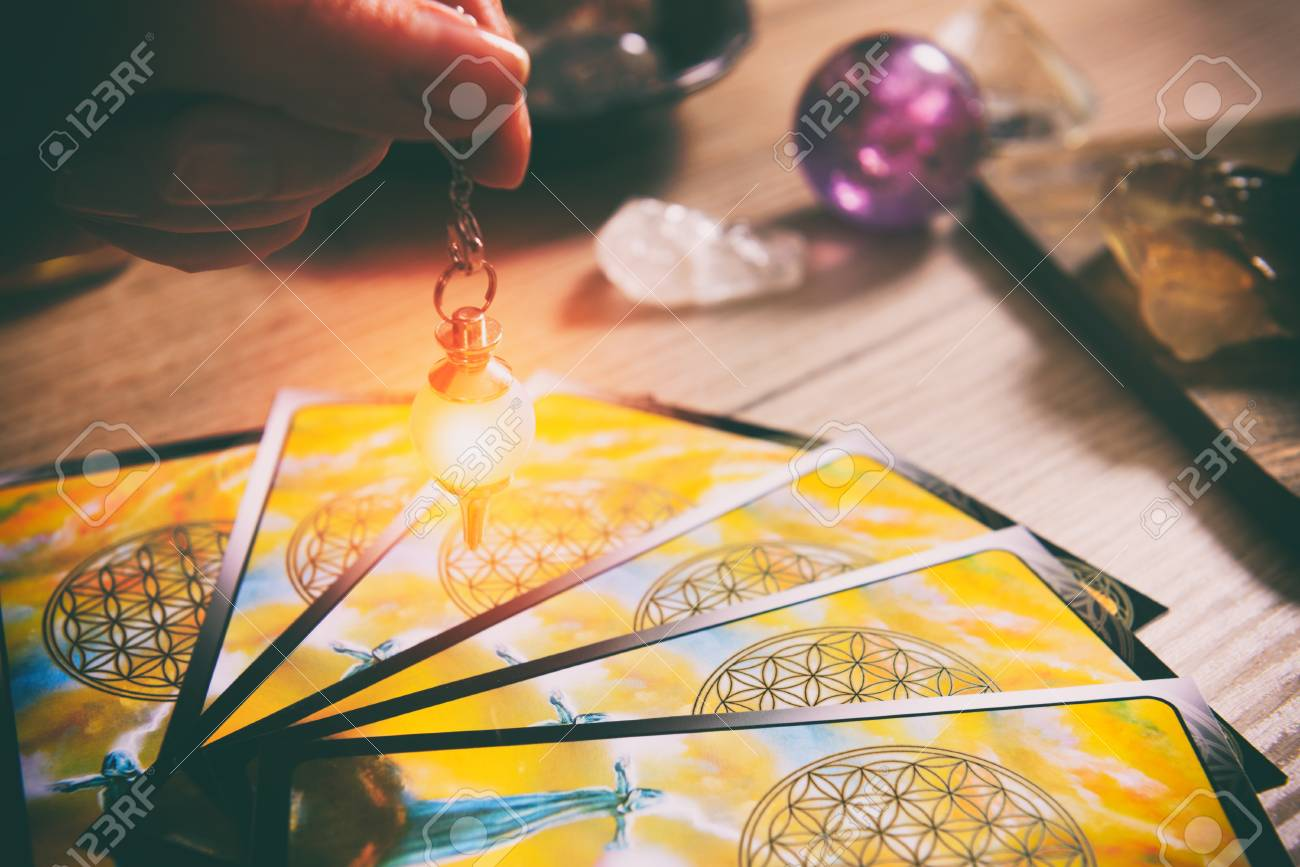 Tarot cards dowsing tool in hand and crystals as a concept of psychic advisor or ways of divination - 101353591