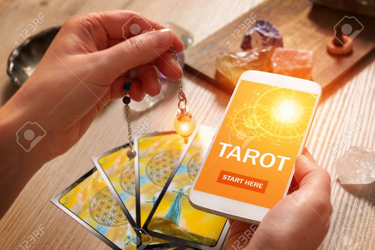 Tarot cards dowsing tool in hand and smartphone with modern fortunetelling application on screen as a concept of psychic advisor or newest ways of divination - 96100547