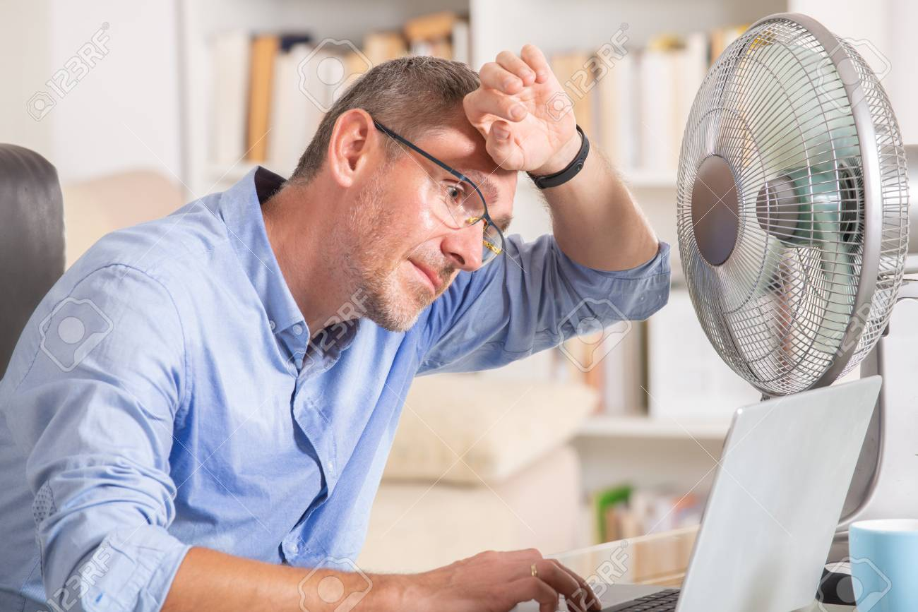 Man suffers from heat while working in the office and tries to cool off by the fan - 104782940
