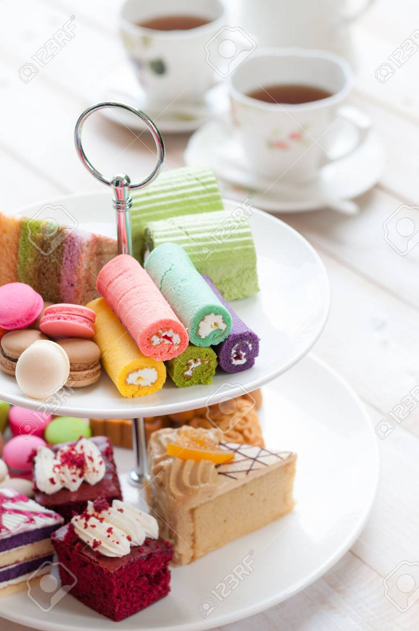 cakes and macaroons on two tiered tray with teapot and cup background - 47440498