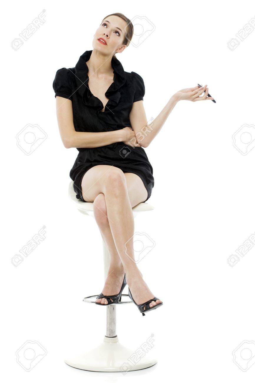 smart young woman sitting on a stool holding a cellphone on white background Stock Photo - 7644950