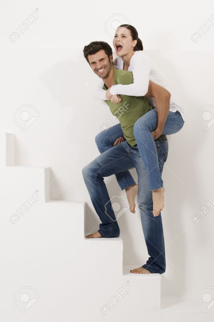 man climbing the stairs with woman on his shoulders Stock Photo - 8549613