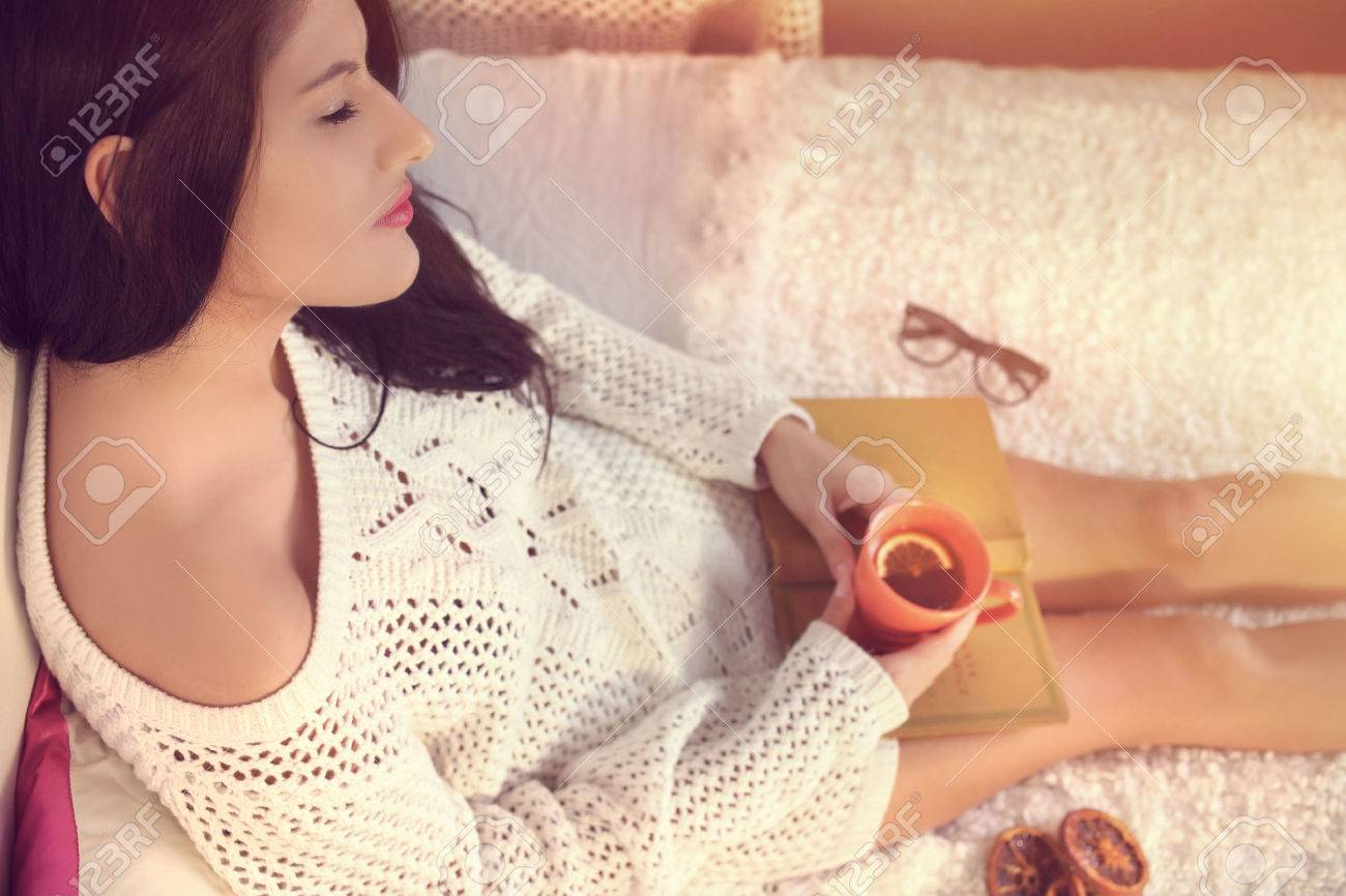 Young girl in a white sweater drinking tea with lemon - 32304786