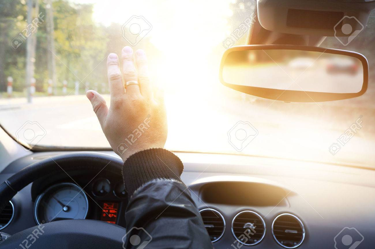 driver blinded by the sun in the car - 33004731