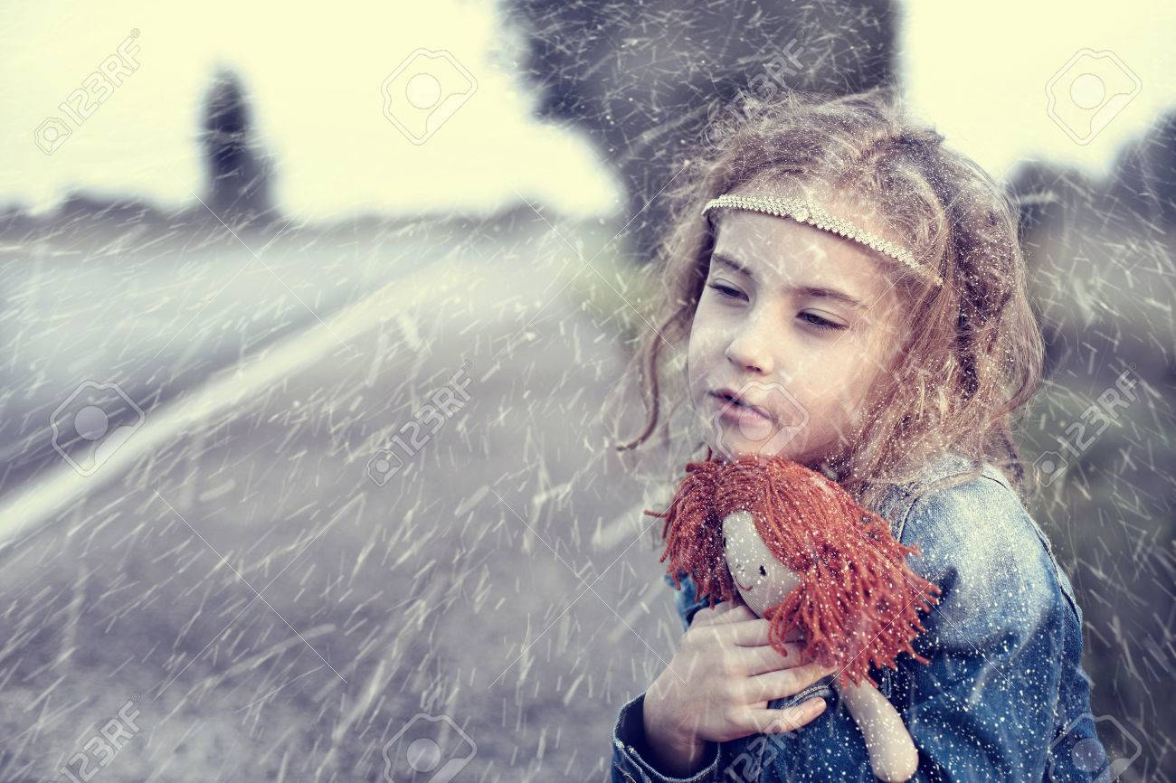 Orphan in the winter snowy day sitting alone outdoors - 33195147