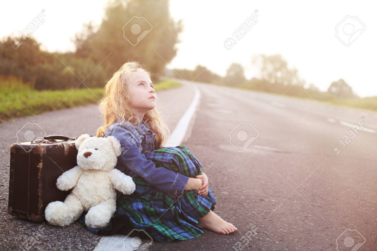 Orphan sits alone on the road with a suitcase - 34280702