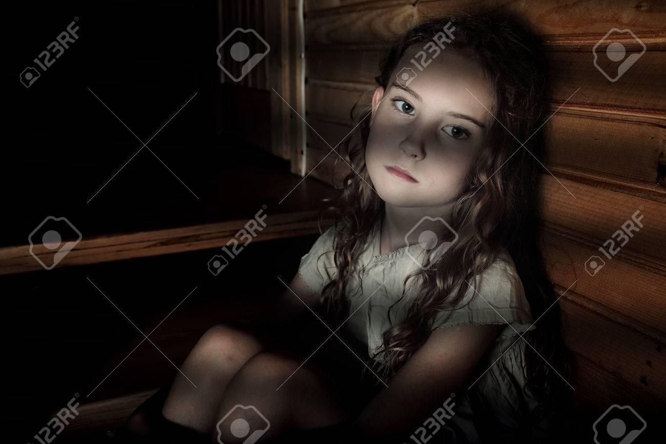 Depressed girl sitting in a dark hallway in home - 45485892
