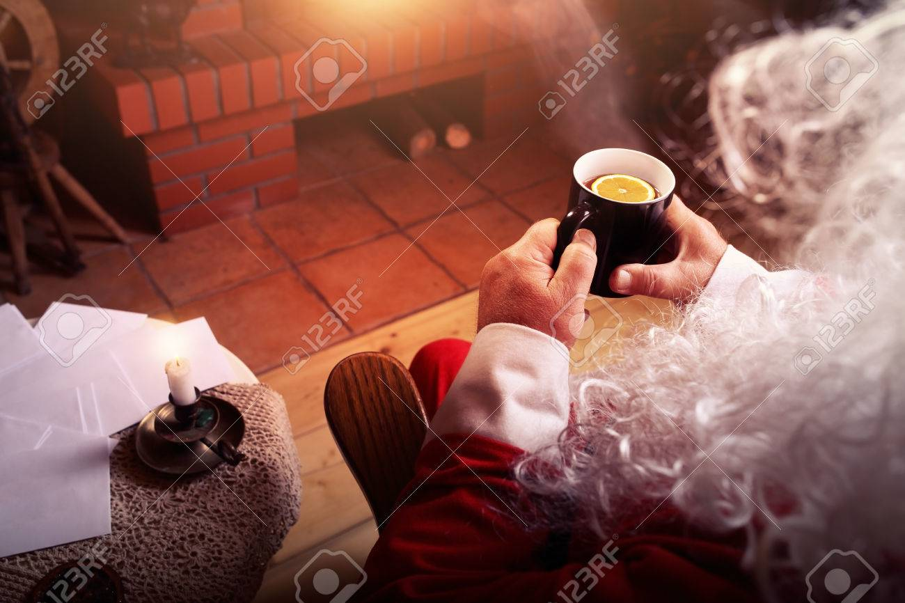 Santa Claus rests in hut with a fireplace and hot tea with lemon - 47426441