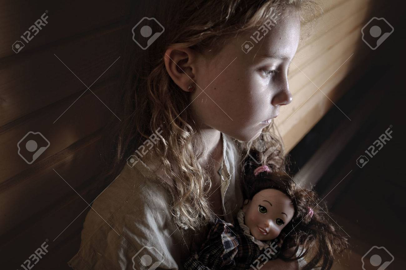 sad little girl with curly hair sitting confused with a doll - 51769359
