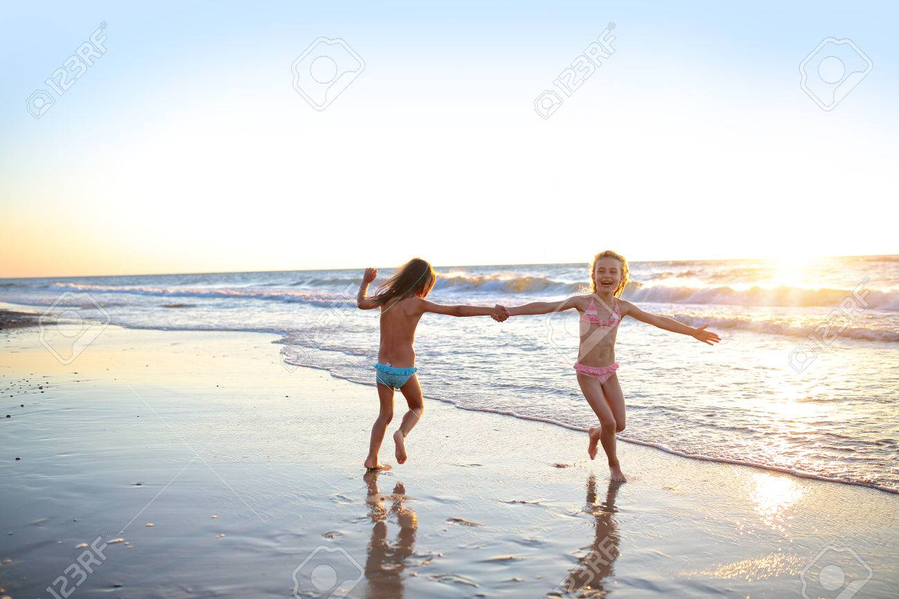 Two sisters dancing on the beach at sunset - 54737441