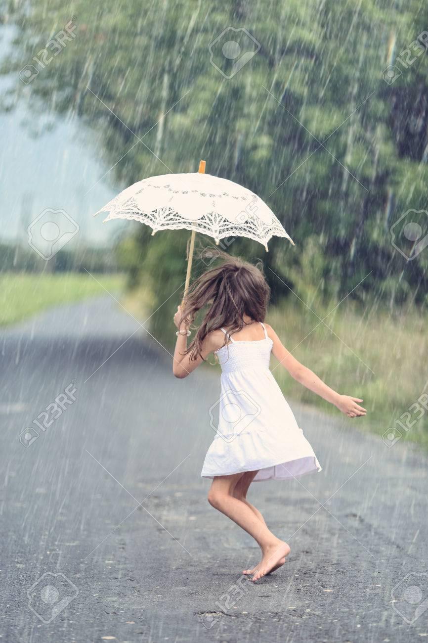 Joyful girl dance with umbrella in rain - 84975435