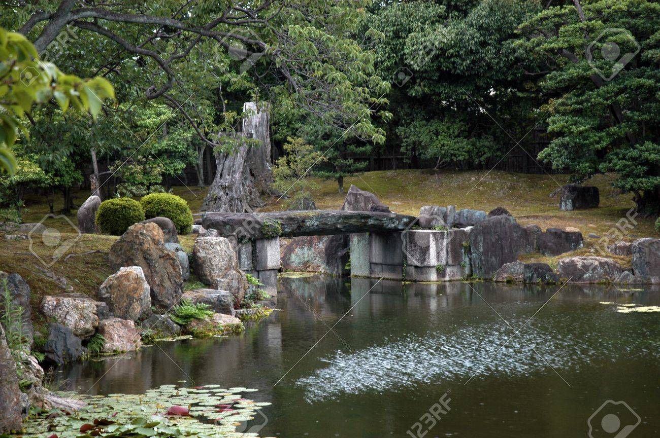 Japanese Garden Stone Bridge japanese garden with stone bridge rocks,and lotus flowers stock