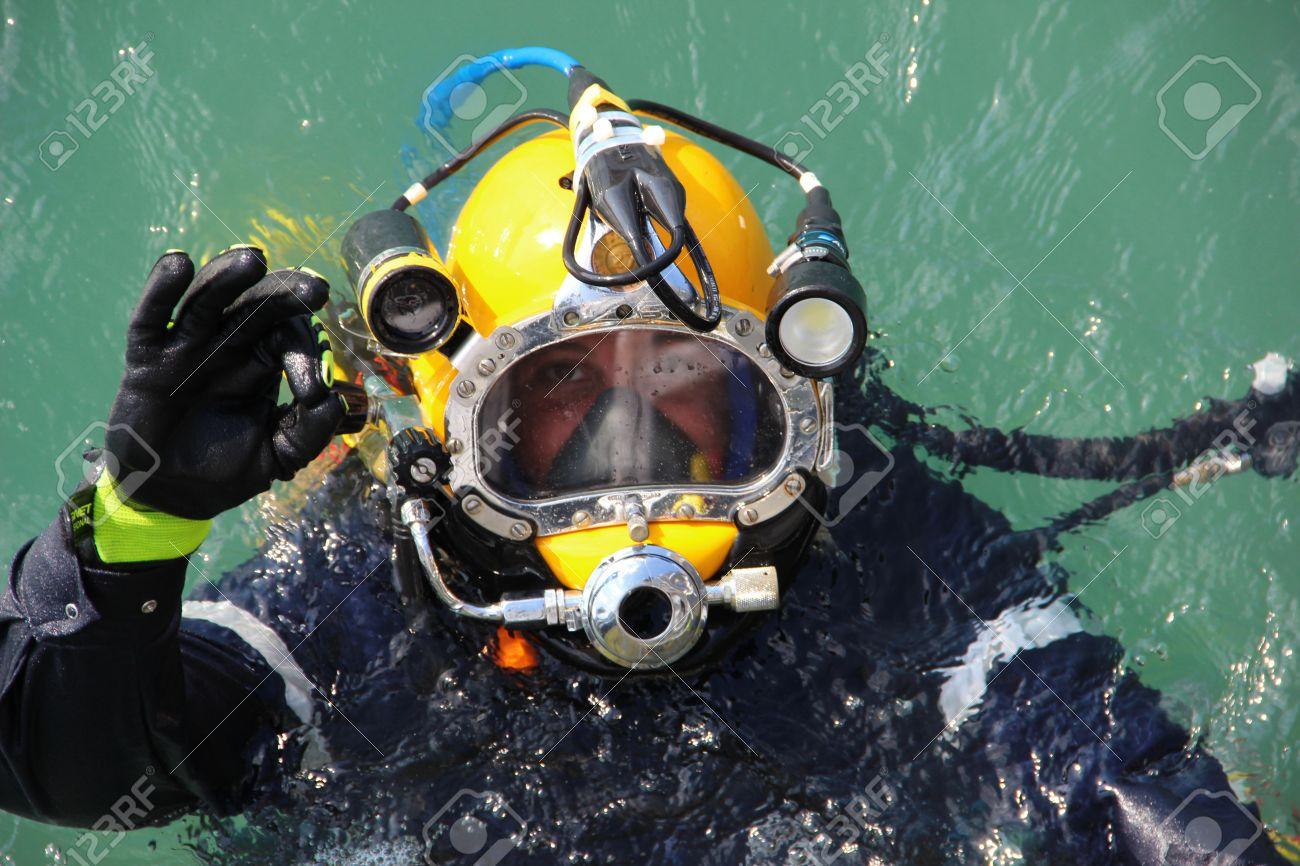 diver in the water in a diving suit and helmet ready to dive and showing sign ok - 61669583