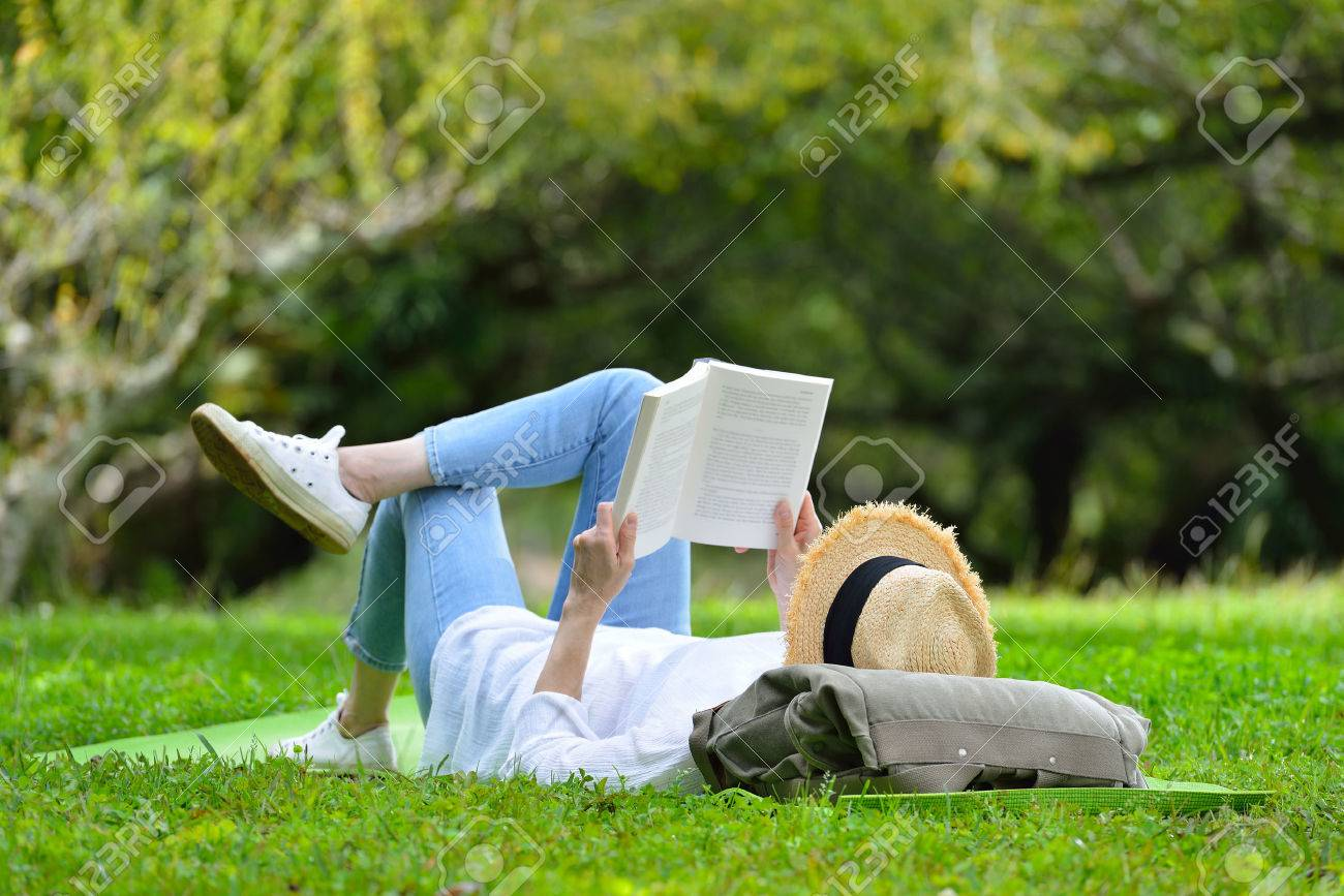 Happy woman lying on green grass reading a book in the park( outdoors ) - 68788846