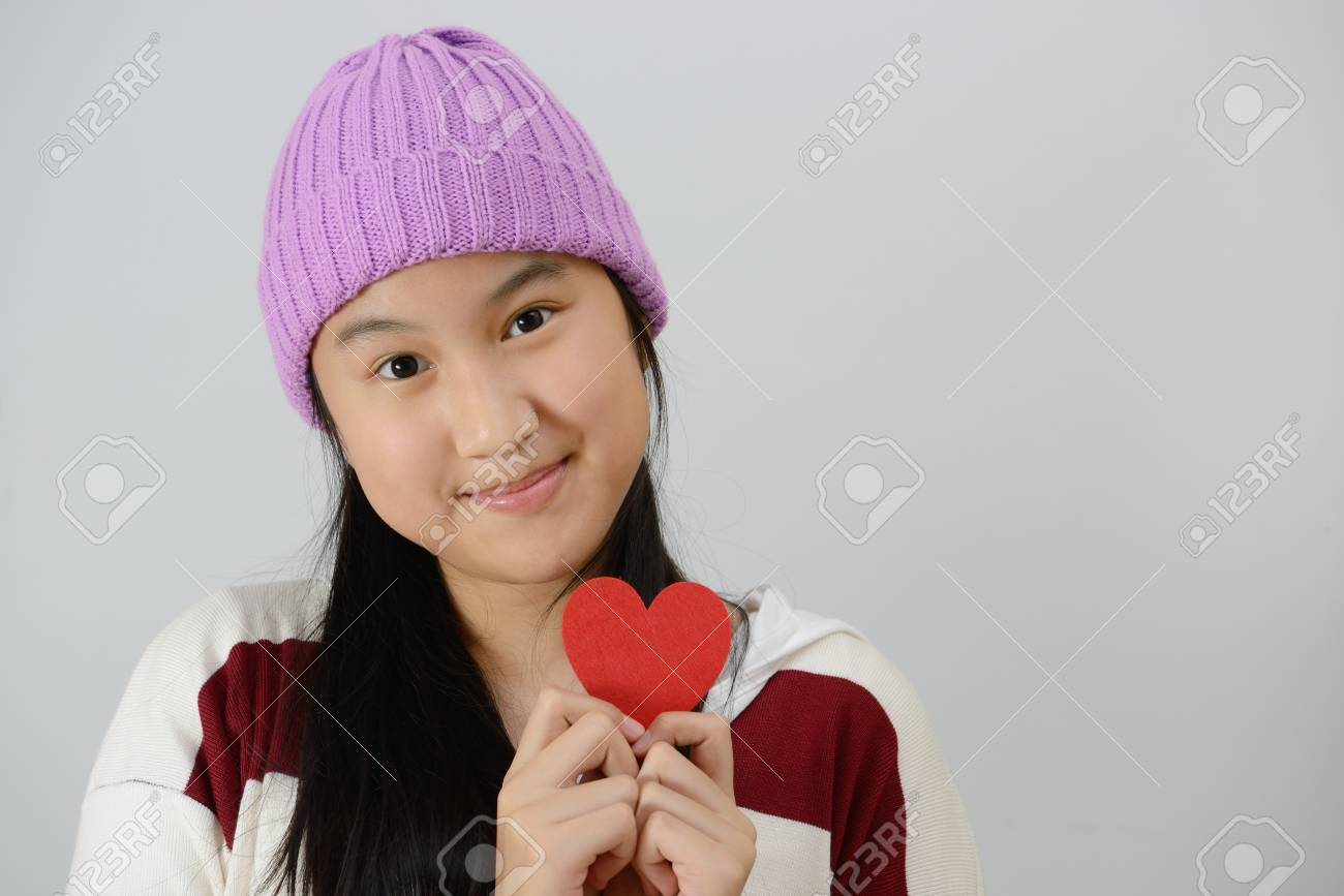 10d75619f9c Beautiful happy smiling teenage girl holding red paper hearts over gray  background Stock Photo - 80053107